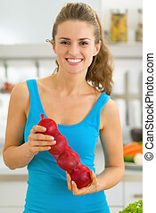 Happy young woman with onion in kitchen