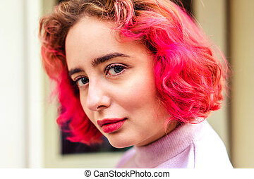 Happy young woman with pink hair in purple dress on a sunny day in the city
