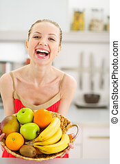 Happy young woman with plate of fruits