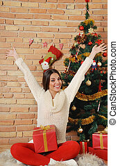 happy young woman with present box on Christmas tree background