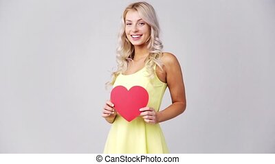 happy young woman with red paper heart