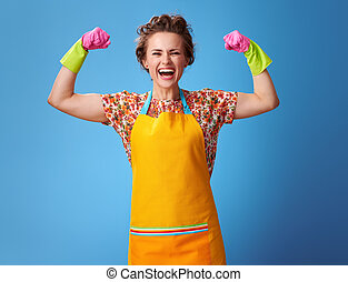happy young woman with rubber gloves on blue showing biceps