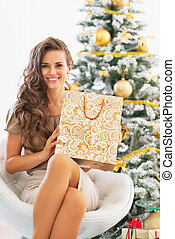 Happy young woman with shopping bag near christmas tree