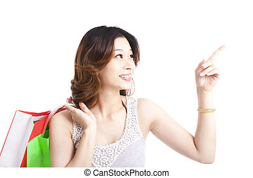 happy young woman with shopping bagand pointing something