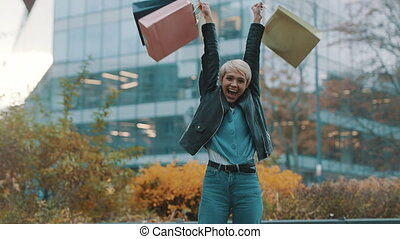 Happy young woman with shopping bags laughing excited in front of the shopping mall