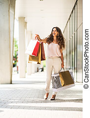 Happy young woman with shopping bags on the mall alley pointing