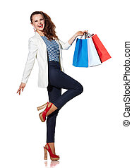 Happy young woman with shopping bags posing on white background