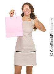 Happy young woman with shopping bags showing thumbs up