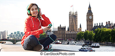 happy young woman with smartphone and headphones - ...