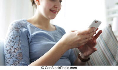 happy young woman with smartphone at home