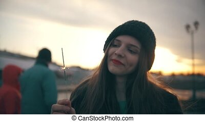 Happy young woman with sparkler at sunset outdoors