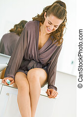 Happy young woman with toothbrush sitting in bathroom