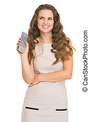 Happy young woman with tv remote control looking on copy space
