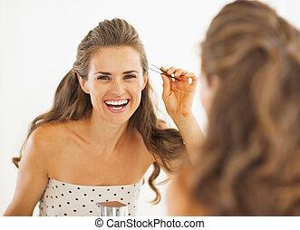 Happy young woman with tweezers in bathroom