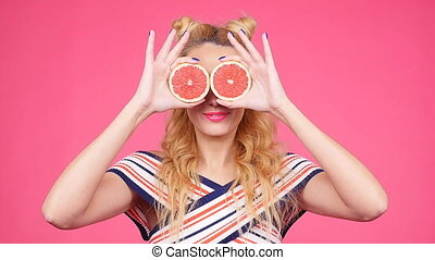 Happy young woman with two half of juicy grapefruit instead eyes