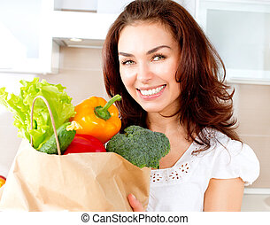 Happy Young Woman with vegetables in shopping bag. Diet...