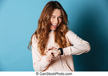 Happy young woman with watch on hand winking.