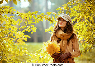 happy young woman with yellow leaves looking up at copy space