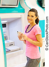 young woman withdrawing cash at an ATM - happy young woman ...