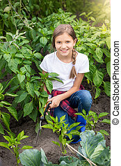 Happy young woman working at garden with trowel