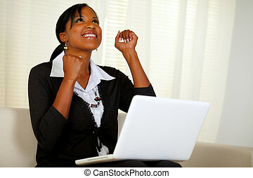 Happy young woman working on laptop and looking up