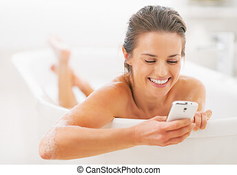 Happy young woman writing sms in bathtub