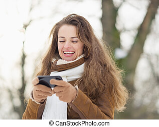 Happy young woman writing sms in winter outdoors