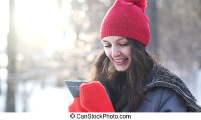 Happy young woman writing sms in winter park