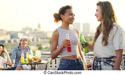 Happy young women are chatting, clinking bottles and drinking standing on rooftop with their friends having fun in background. Millennials, joy and summer concept.