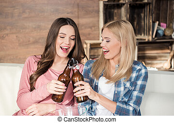 young women clinking beer bottles while sitting on couch