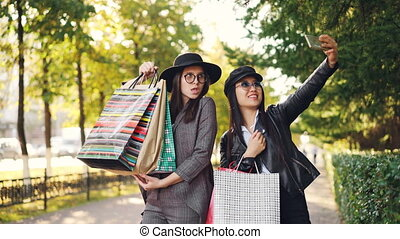 Happy young women friends are taking selfie with paper bags standing outdoors on sidewalk and posing. Girls are using smartphone and wearing casual clothing.