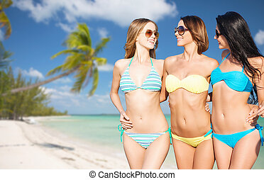 happy young women in bikinis on summer beach