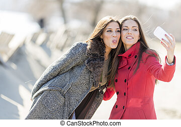 Happy young women taking photo with mobile phone