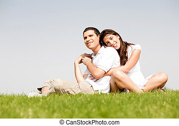 Happy young women with arms around her husband and laying on...