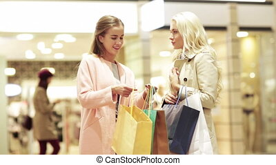 sale, consumerism and people concept - happy young women showing content of shopping bags in mall
