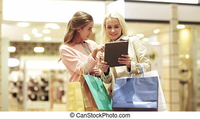 happy young women with tablet pc and shopping bags