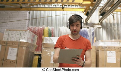 Happy young worker in industrial warehouse listening to...