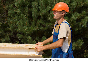 Happy young workman on a building site carrying a wooden wall insulation panel with a smile, side view against greenery with copyspace