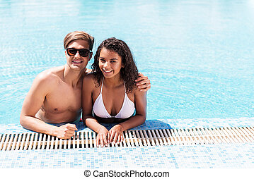 Happy youthful couple relaxing together in water