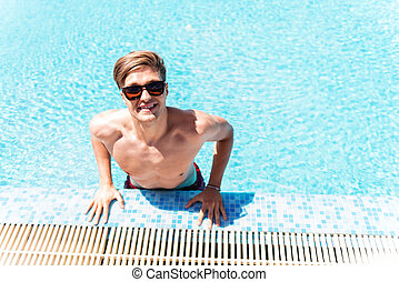 Happy youthful guy having rest in water outdoor