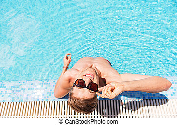 Happy youthful guy relaxing in water outdoor