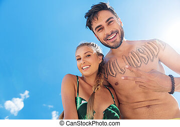 Happy youthful man and woman having fun on beach