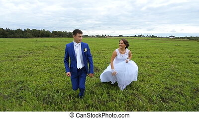 Happy,newlyweds couple running on a green meadow field