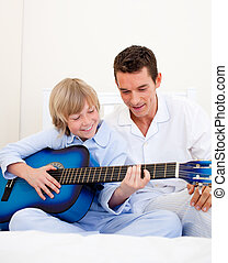 Happyy little boy playing guitar with his father