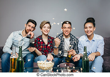 hapy young people are spending time in front of TV.
