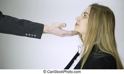 Harassment in office. boss touching chin to young employee.