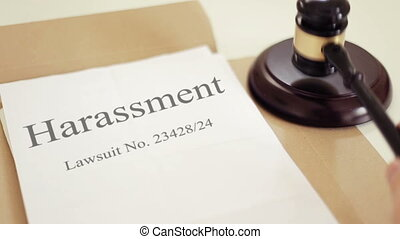 Harassment lawsuit verdict folder with gavel placed on desk of judge in court