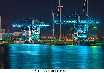 Harbor cranes at night - Wharf during twilight with huge...
