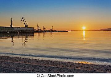 Harbor cranes at sunset