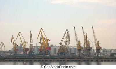 Harbor cranes on sky background.